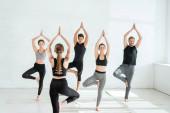 Rückansicht eines Yoga-Trainers, der vor jungen Leuten steht, die Baumposen üben