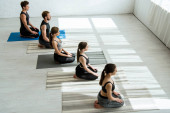Fotografie high angle view of five young people meditating in thunderbolt pose