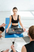 Photo young people meditating in half lotus pose near vase with aromatic sticks