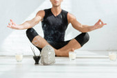 Fotografie selective focus of young man practicing yoga in half lotus pose near decorative buddha head, aromatic sticks and candles