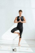 handsome young man practicing yoga in tree pose near decorative buddha head, aromatic sticks and candles