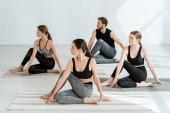 čtyři mladí lidé cvičí jógu v polopáteřní twist pózovat ve sportovním centru