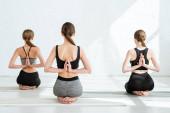 Rückansicht junger Frauen, die in Diamant-Pose mit gebeteten Händen hinter dem Rücken üben
