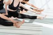 ostříhaný pohled na mladé lidi ve sportovním oblečení cvičit jógu v ohybu dopředu póza