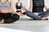 částečný pohled na mladé ženy a muže cvičící jógu v pololotosovém póze