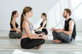 oldal nézet a fiatalok gyakorló jóga féllótuszpózban