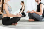 cropped view of young people practicing yoga in half lotus pose