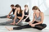 Jugendliche in Sportkleidung praktizieren Yoga in Beinstreckpositionen