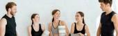 panoráma lövés mosolygós nők jóga szőnyeg áll közel jóképű férfiak