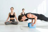 Photo young man practicing low push up plank pose on stands, and women sitting in half lotus pose