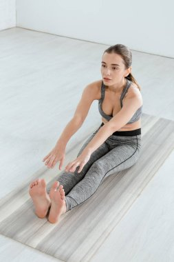 young woman in sportswear practicing yoga in seated forward bend pose