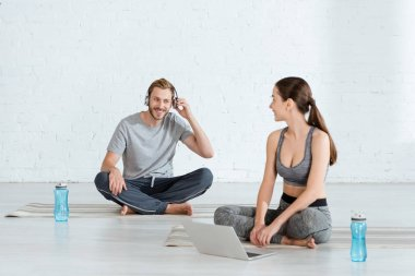 cheerful man in headphones and woman with laptop sitting in easy poses