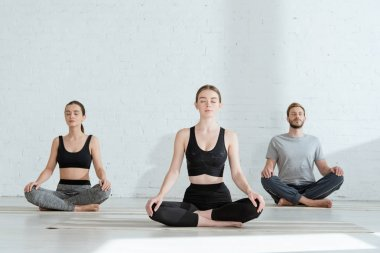 young men and woman practicing yoga in half lotus pose