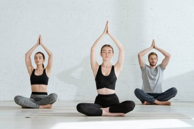 young men and woman practicing yoga in half lotus pose with raised prayer hands