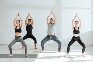 young people in sportswear practicing yoga in goddess pose with raised prayer hands
