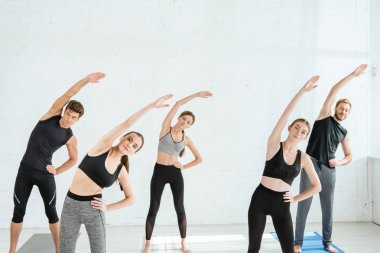 five young people doing side tilt in star pose with hand on hip