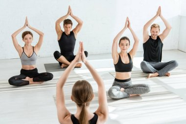 back view of yoga instructor showing young people half lotus pose with raised prayer hands