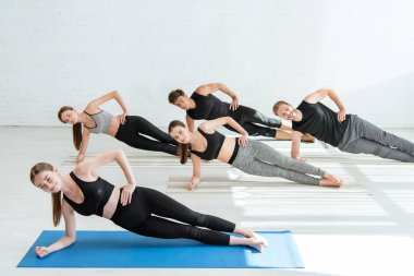 five young people practicing yoga in side plank pose