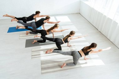 high angle view of five young people practicing yoga in balancing table pose