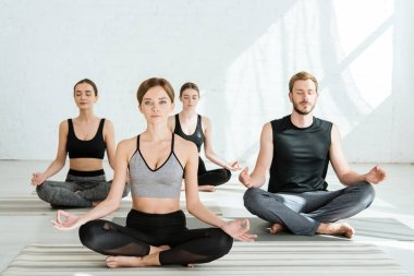 front view of young people practicing yoga in half lotus pose