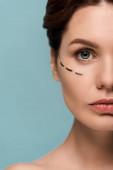 Fotografia Cropped vista della donna con linee marcate sul viso isolato sul blu