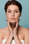 Fotografia bella giovane donna che tocca il viso con linee marcate isolate sul blu