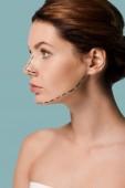 Fotografia giovane donna con linee marcate sul viso guardando lontano isolato sul blu