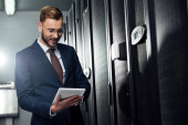 selective focus of cheerful businessman in suit using digital tablet in data center