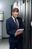 Fotografie obchodník v obleku pomocí digitálního tabletu v datovém centru