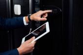 Fotografie oříznutý pohled na muže držícího digitální tablet a ukazujícího prstem na digitální panel