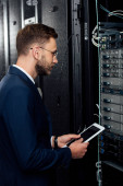 handsome businessman in glasses holding digital tablet and looking at database in server rack