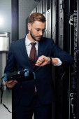 Photo handsome businessman standing with reflectometer and looking at watch in server room