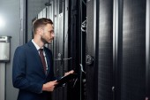 Photo selective focus of handsome businessman in glasses and suit holding clipboard and pen in data center