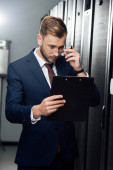 Photo handsome businessman touching glasses while looking at clipboard