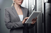 Photo cropped view of businesswoman holding digital tablet in server room