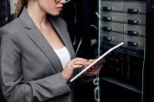 vista ritagliata di businesswoman utilizzando tablet digitale vicino rack server