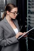 beautiful businesswoman using digital tablet near server rack