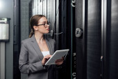Photo selective focus of businesswoman in glasses holding digital tablet near server racks