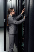 Photo attractive businesswoman in glasses looking at server rack in data center