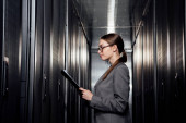 Photo side view of businesswoman in glasses holding clipboard in data center