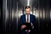 Photo handsome businessman in glasses looking at clipboard near server racks