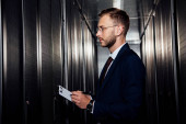 Photo side view of businessman in glasses holding clipboard near server racks