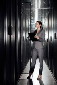 Photo beautiful businesswoman holding clipboard while standing in data center