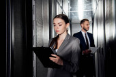 Photo selective focus of attractive businesswoman holding clipboard near businessman in data canter