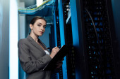 Photo beautiful businesswoman writing while holding clipboard in server room