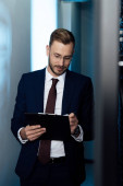 Photo bearded businessman in glasses holding pen and clipboard in data center