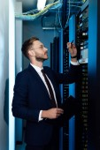 Photo profile of handsome businessman in glasses holding pen and clipboard while looking at server rack