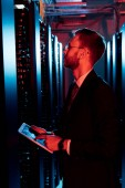 Photo side view of bearded man in glasses holding digital tablet in server room
