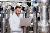 jóképű szakállas mérnök fehér kabátban gazdaság laptop