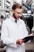 bärtiger Ingenieur im weißen Mantel mit Stift in der Nähe von Klemmbrett und Druckluftanlage